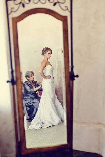 Stunning Wedding Photography Ideas - a mother adding the finishing touches to bride's dress view in the mirror...