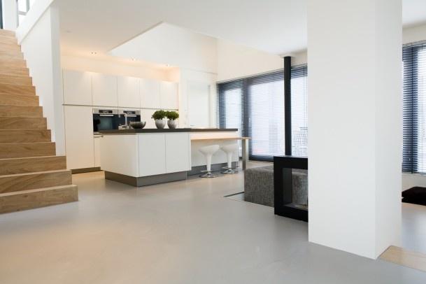 Gietvloer met houten trap en moderne keuken.