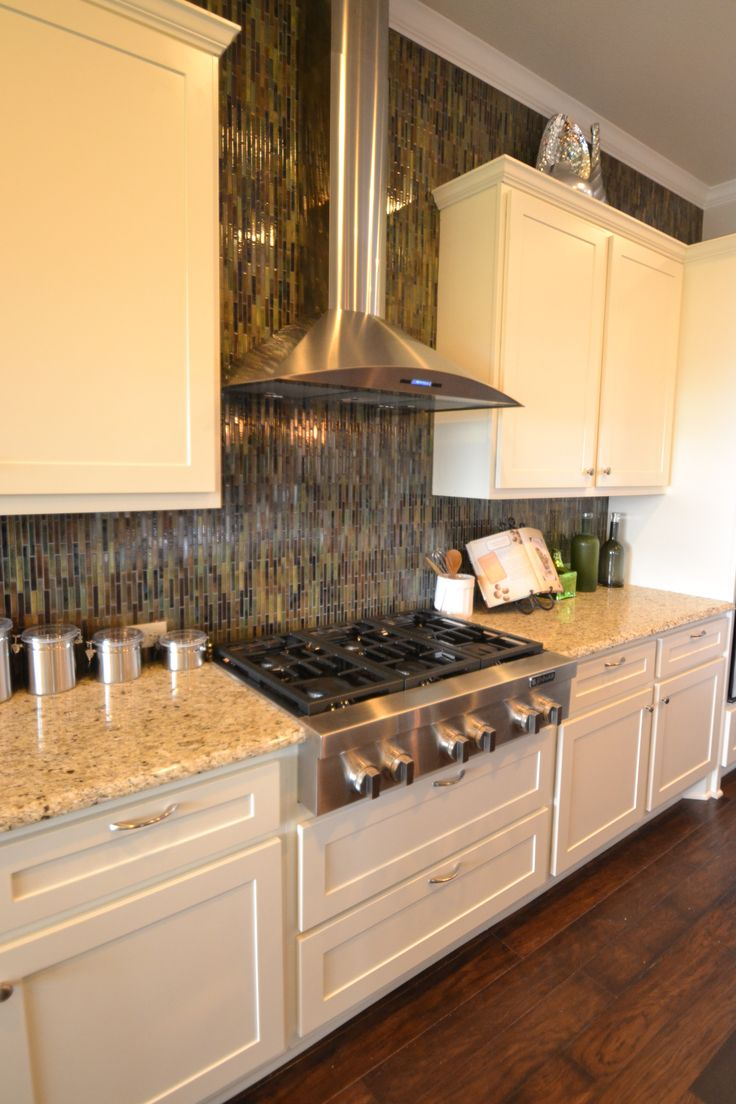 Granite counter tops, stainless steel cook top and vent in this model home in Driftwood Texas.