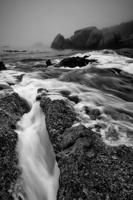 Smooth, silky water flows in through the seaside rocks as the tide rises