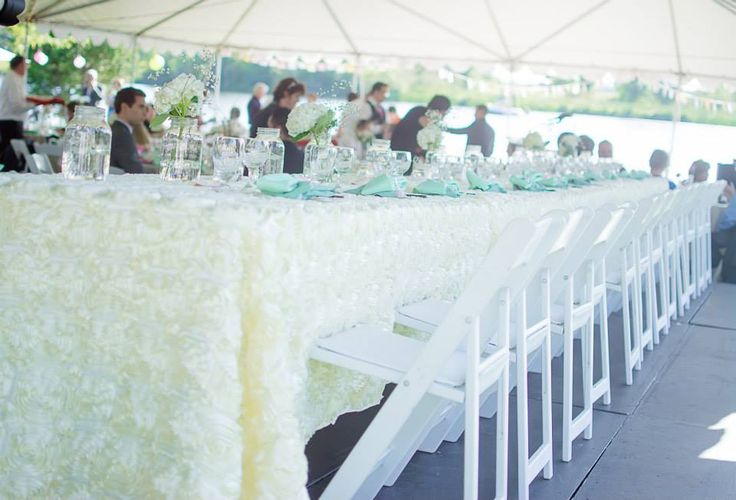 White folding chairs. Backyard wedding. Ivory rosette linens. Tent reception. Photo by Eleventh Hour Photography
