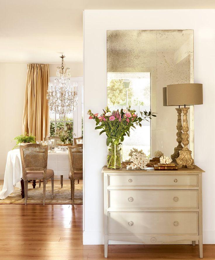 Recibidor con espejo envejecido y flores sobre la consola. Clásico y lleno de luz