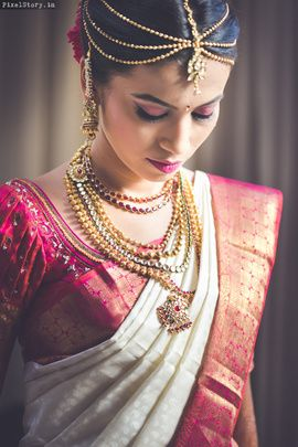 South Indian bride. Gold Indian bridal jewelry.Temple jewelry. Jhumkis.Pink and white silk kanchipuram sari.Braid with fresh jasmine flowers. Tamil bride. Telugu bride. Kannada bride. Hindu bride. Malayalee bride.Kerala bride.South Indian wedding.