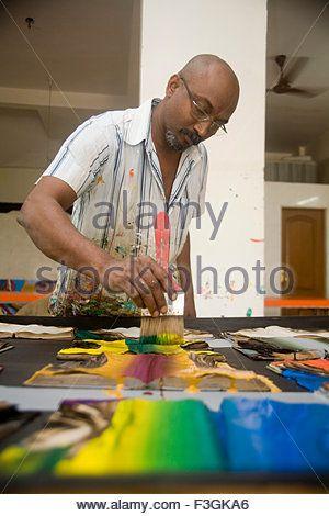 Indian contemporary artist Bose Krishnamachari in his studio working on canvas ; Bombay Mumbai ; Maharashtra - Stock Photo