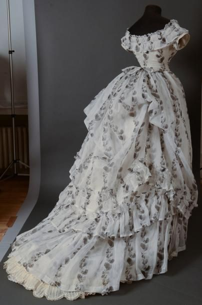 Dress of the afternoon, around 1874, in cream organza printed in black rising garlands medlar; bodice edge stapled to round skirts, boat neckline emphasized gathers and of a wheel, handlebars taped. Ruffled skirt turn to small train, apron draped with beautiful transparency effects and overlay printed decoration, links attached upside down on used to control the movement of the top of the draped figure, (superb condition, few small holes).