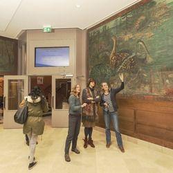 Muurschildering binnenkomst hal met uitleg van restaurators