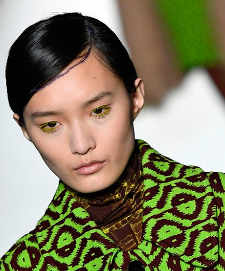 The Trend: Dries Van Noten's Pretty Plumes—Perfect festival hair, anyone? The daintiest neon feather creeps along a deep side part for a high-fashion-meets-boho take on a low bun.