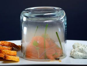 The raw salmon is smoked tableside under a glass with mesquite smoke using the Smoking Gun
