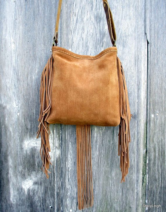 Small leather cross body bag in a honey brown, suede leather. The front of the bag has 7, hair on cowhide, triangles that Morgan has hand sewn with her beautiful saddle stitch. The corners of the triangles are accented with dome studs. The hides are in a variety of brown and white, hair on, calf skin. Matching suede fringe on the sides and front. The bag has an adjustable, simple leather strap that will adjust from 42.5 to 48.5. The bag is 9 tall by 9 across with a 2.5 bottom. It is fully…