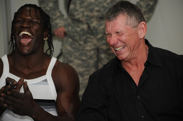 """World Wrestling Entertainment (WWE) wrestler Ron Killings (left) also known as """"R-Truth"""" and Vincent McMahon Sr. (right) share a laugh at Forward Operating Base (FOB) Loyalty, Beladiyat, eastern Baghdad, on Dec. 4, 2008. The WWE wrestlers stopped at FOB Loyalty to sign autographs and pose with Soldiers for photographs. (U.S. Army photo by Staff Sgt. James Selesnick/Released)."""