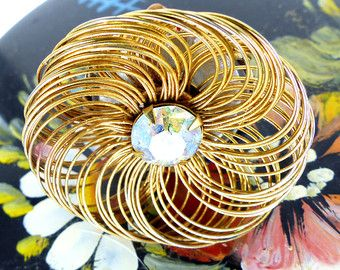Magnetic Mag TAK™ iridescent faceted crystal set in a gold wired spiral design. Silk button back. Hat pin, brooch or choker embellishment