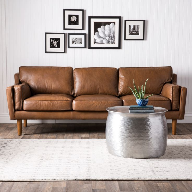 This soft sofa is composed of luxurious Oxford leather upholstery in a tan color with polyurethane foam, duck feathers and polyester fiber couched within. The sturdy wood legs are are finished in a lovely and bold oak finish.