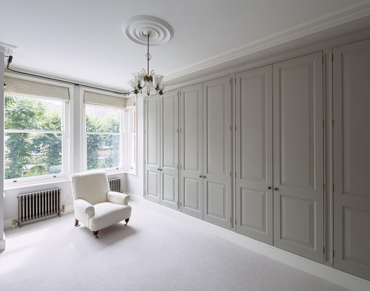 Master bedroom bespoke wardrobes, timber doors with raised and fielded paneling hung on butt hinges, spray white finish carcases