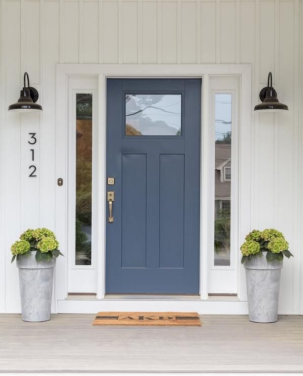 Glossy Black Vintage Barn Sconces Are Mounted To A White Paneled Home Exterior On Either Side Of Blue Front Door Accented With Single Gl Panel
