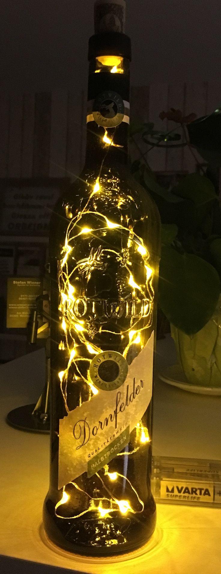 Rotweinflasche 0,7 L als LED Flaschenlampe!  Diese Beleuchtungsvariante ist einfach ein Eyecatcher! Eine filigrane LED-Ketten werden in Handarbeit in die Flaschen eingefügt, ein kleines, verschlossenes Loch auf der Rückseite der Flasche lässt das Kabel zum Batteriekästchen durch. Die Lichterkette wird mit  3 AA Batterien betrieben. Ausführung Lichterkette hier mit 40 LED.
