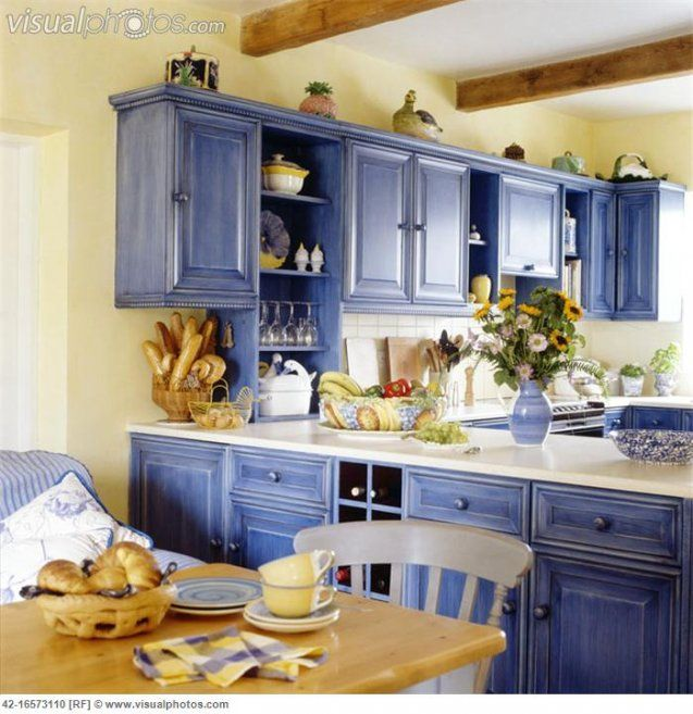 Elegant Interior Design With A Kitchen Shelf And Blue Kitchen Cabinets And  Kitchen Tables And Cooking Utensils And A Dining Table And Chairs And A  Vase Of ...