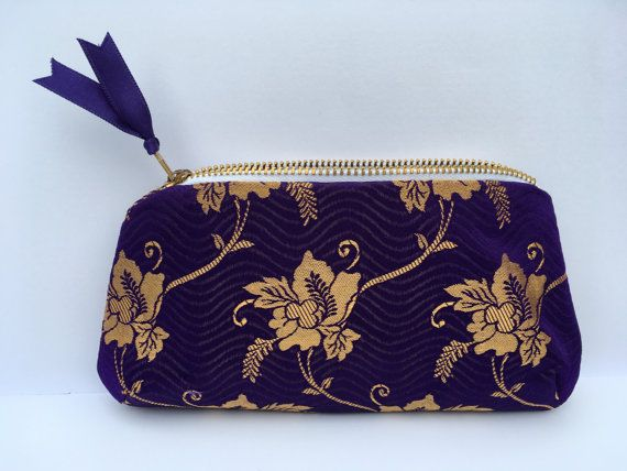 Handmade sari fabric purse, or could be used as a small clutch bag or cosmetic bag. Made from beautiful silky feel purple and gold fabric, an ideal gift. Rounded base adds interest to the purse shape. Metal zip closure, lined with handy inside patch pocket. . 19cm wide at base x 10cm. Zip opening 14cm . YKK metal zip . Purple and gold coloured polyester sari fabric outer . Same fabric is used for both front and back . Purple polyester lining . Inside patch pocket 10cm x 6cm . As each item is…