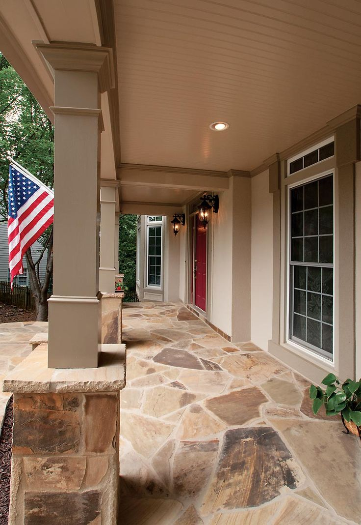 Interior view of new front porch with wood columns and stone bases, flooring. Designed and built by Georgia Front Porch.