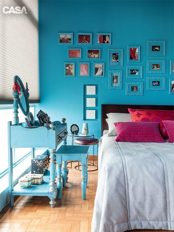 A parede da cabeceira deste quarto é toda coberta com fotos e postais emoldurados
