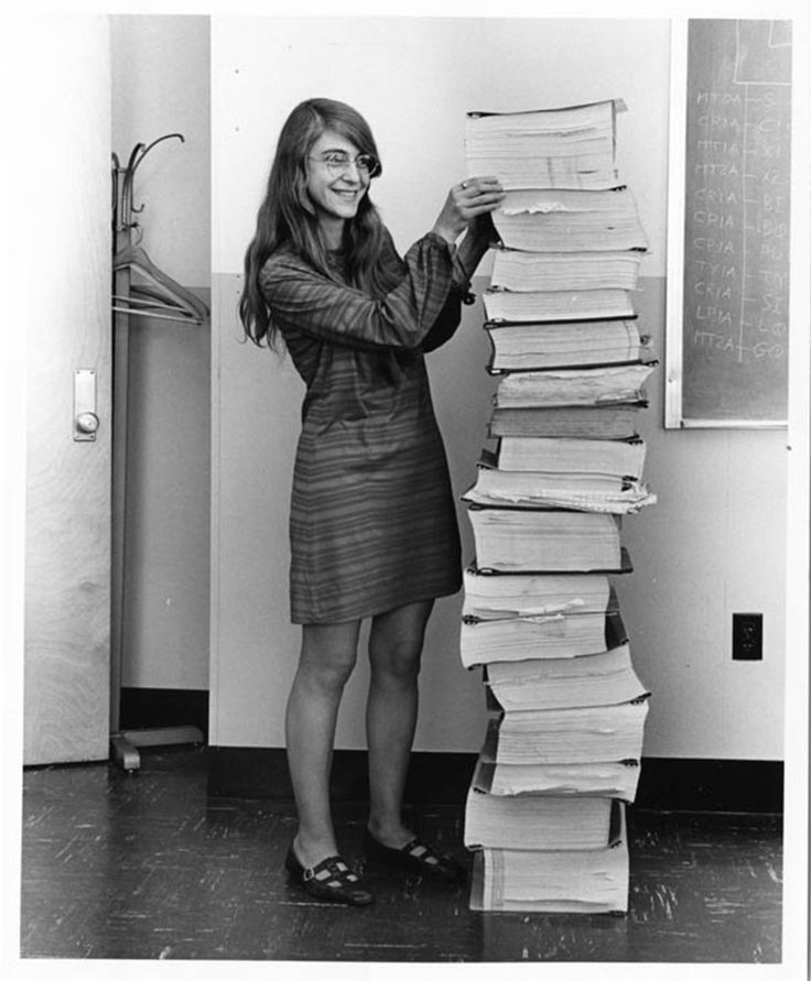 Margaret Hamilton (MIT soft wear engineer) stands next to a stack of Apollo Guidance Computer source code.