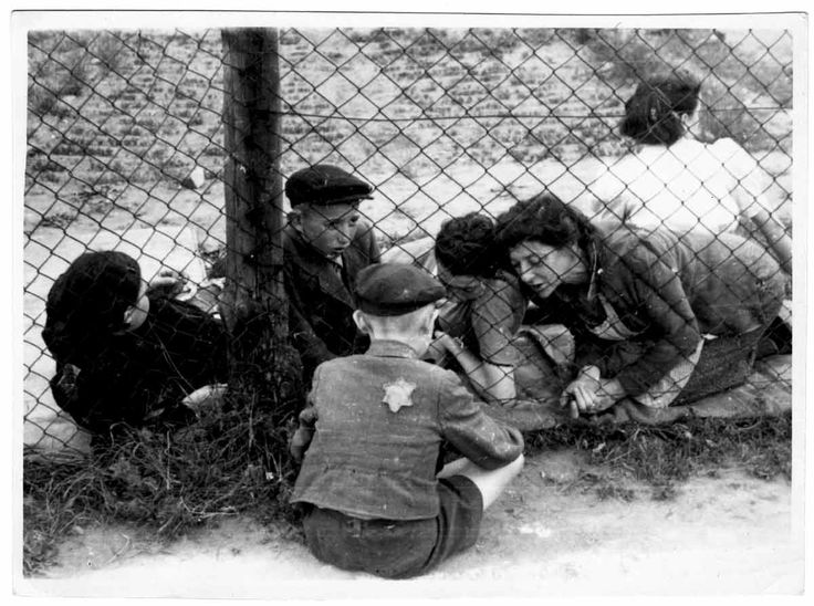 A Jewish family says goodbye to a young boy through a wire fence in the Lodz…