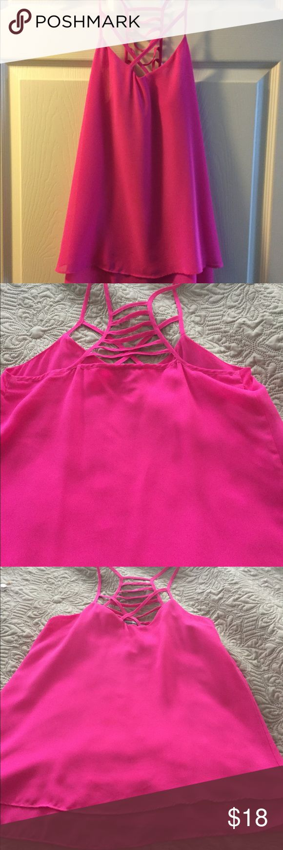 Hot pink strappy top. Bright pink. Strap detailing on the front and the back. Tiered at bottom but not long. Cute with distressed jeans . Tops