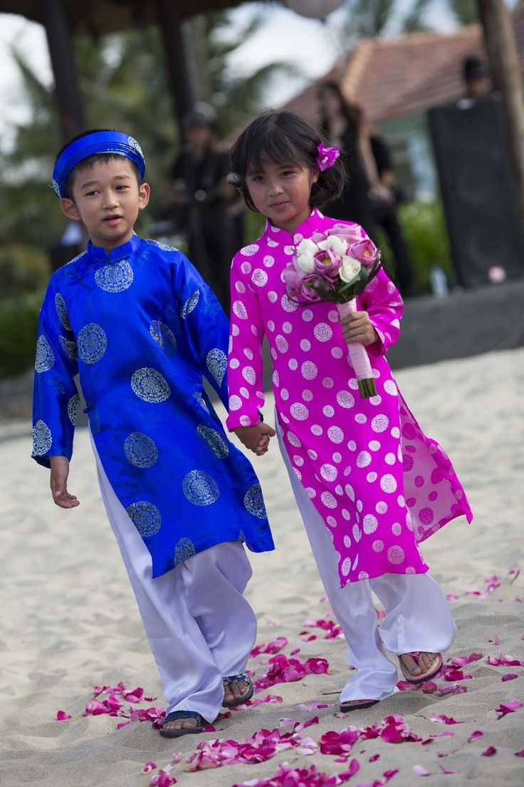The youngest of the bridal party walk down the aisle in royal blue and pink traditional Vietnamese dress. #HoiAnEventsWeddings #HoiAn #VietnamBeachWeddings