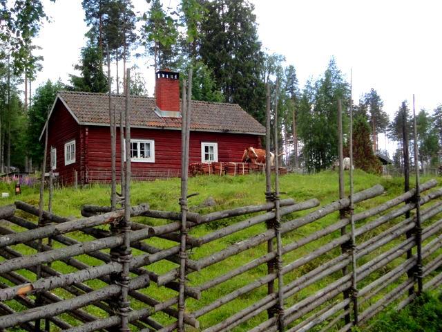 Swedish summer farm. Round pole spruce fence.