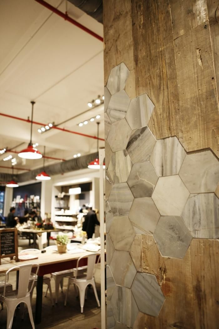 The café's structural supports are clad in a combination of reclaimed wood and hexagonal marble tile.
