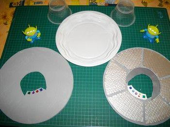 soucoupe volante flying saucer materiel : - carton plume - carton - assiette plastique - pot transparent (ile flottante Senoble) - strass (les boutons de commande) - peinture - 2 aliens (Toy Story) - colle