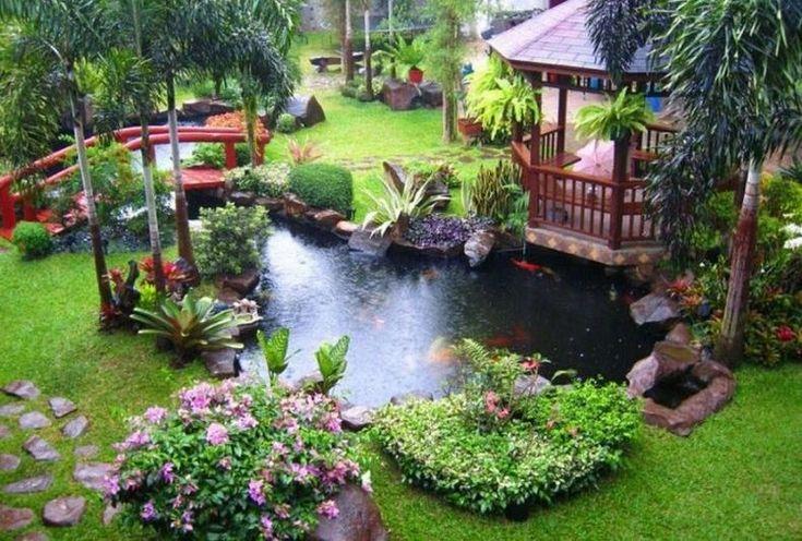 bassin d'eau avec palmiers, fleurs, plantes vertes et pont en bois massif…