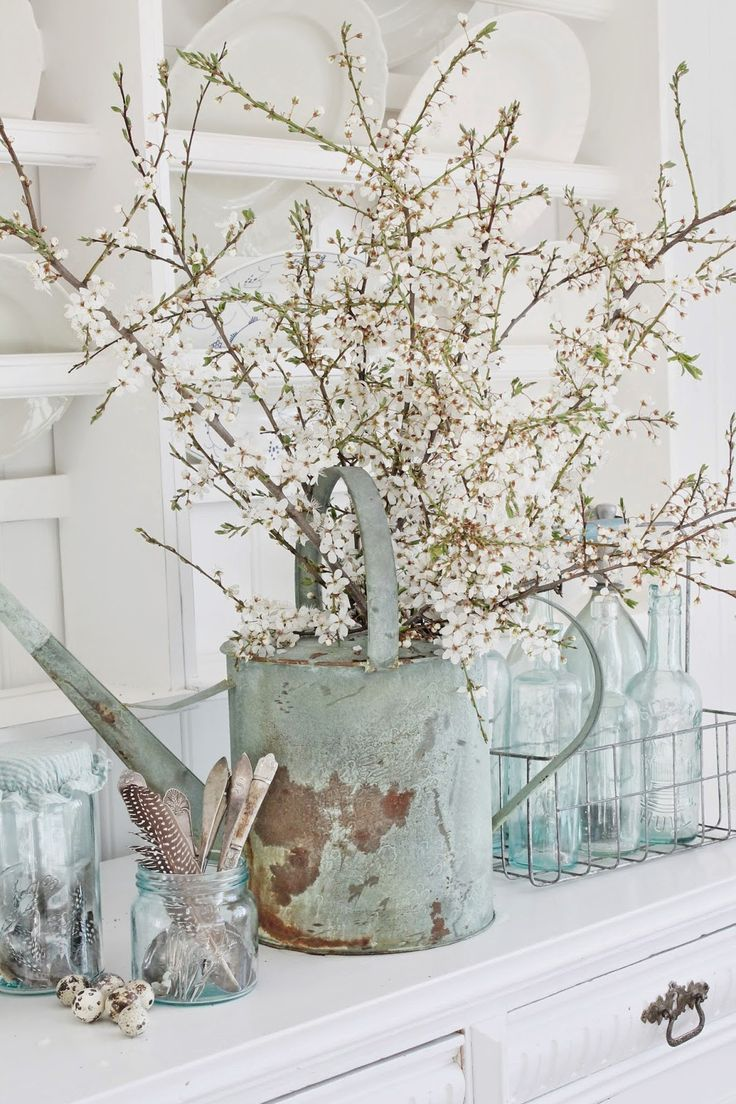 Love the chippy blue paint on the watering can mixed with the rustic white floral arrangement