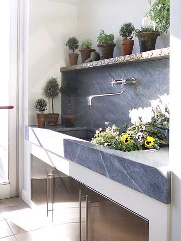 Mudroom - This soapstone counter with a doublewide, extra deep integrated sink is a great asset. With the vegetable garden just steps away and two dogs who love baths, the sink will be quite useful.  As a trained floral designer who loves fresh flowers in the house year round, I know I can put it to use as shown.  <3 the glass door allowing the natural light to shine in. #bhg.com