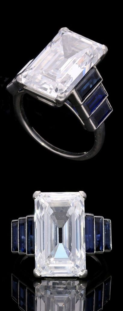 An Art Deco diamond and sapphire ring, circa 1920. Featuring an exceptional 10.28ct emerald-cut 'Golconda' diamond with graduated sapphire shoulders. #ArtDeco