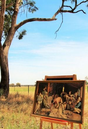 A print of Tom Robert's famous 3 of 3 painting on an easel at the location where the woolshed featured in the painting stood prior to being destroyed by fire in the 1960s.