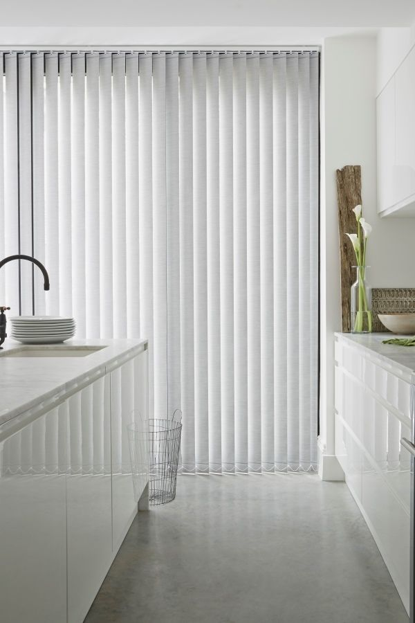 Stark white decor create a beautiful minimalist interior, add hints of black and natural materials such as wood and stone to add depth to the look. Made to measure white Verticals add a lovely finishing touch to the room.