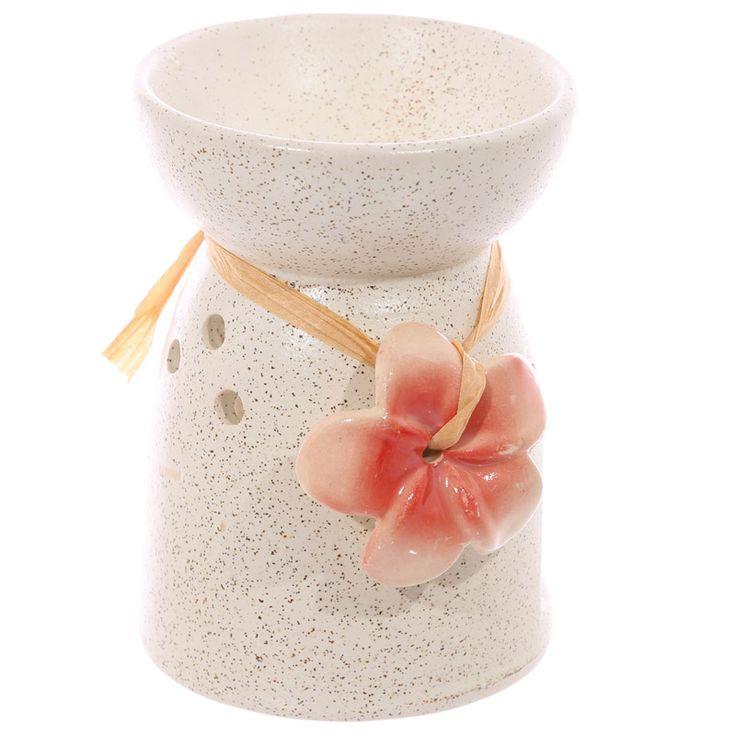 Een leuke Wax-Melt Brander van keramiek. Deze Wax-Melt brander  is versierd met een bloem van keramiek welke om de oliebrander gebonden is.    Dankzij het grote gat in de brander kunt u het waxinelichtje zonder gevaar in de brander zetten en komt er voldoende zuurstof in de brander. De hitte die ontstaat zal de geur wax-melt laten smelten en verspreidt zo de geur.    Vorm: rond Materiaal: keramiek Kleur: crème  Bloem: Rood  Hoogte:  ca 11 cm Diameter: ca 8 cm
