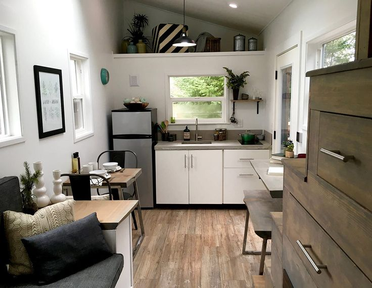 This tiny house features an electric fireplace and natural hardwoods throughout. A custom staircase and storage loft provide plenty of storage space.