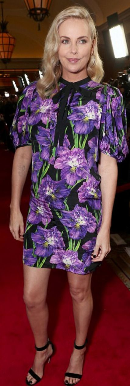 Who made Charlize Theron's black sandals, jewelry, and purple floral dress?