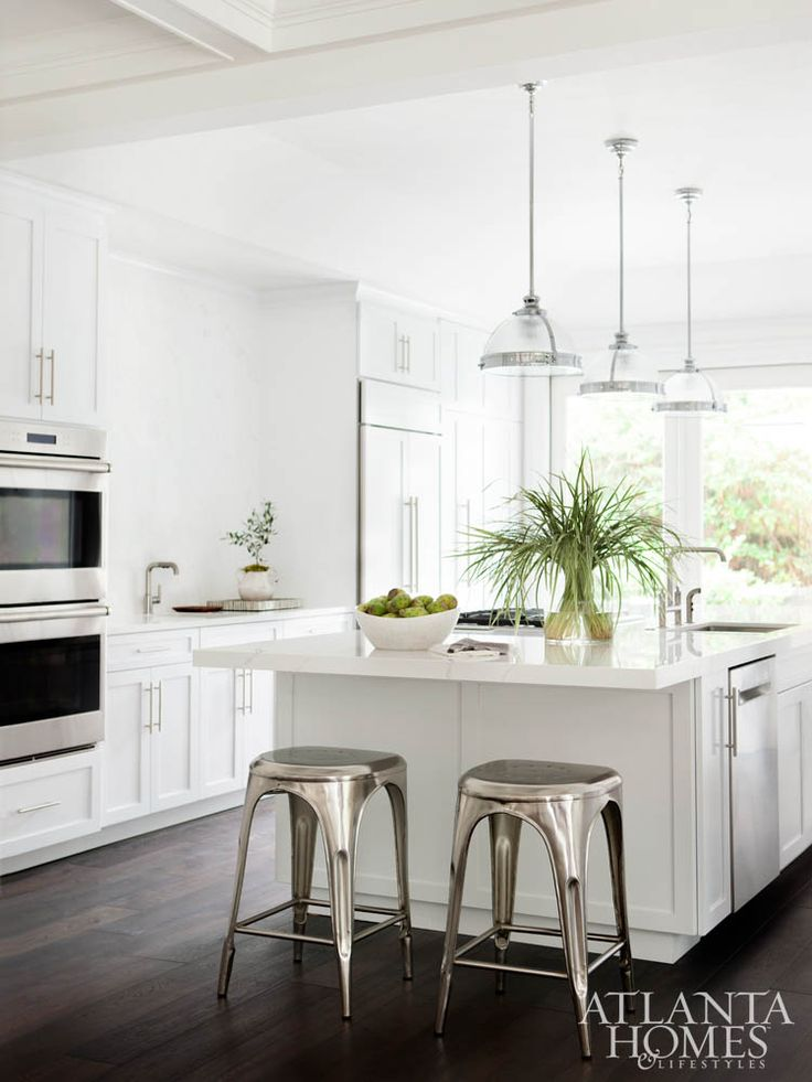 Beautiful classic kitchen with dark wood floors, white cabinets, pendant lighting