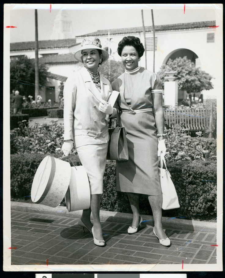 African American woman wearing hat and carryng two hat boxes posing with another woman, Los Angeles, ca. 1951-1960