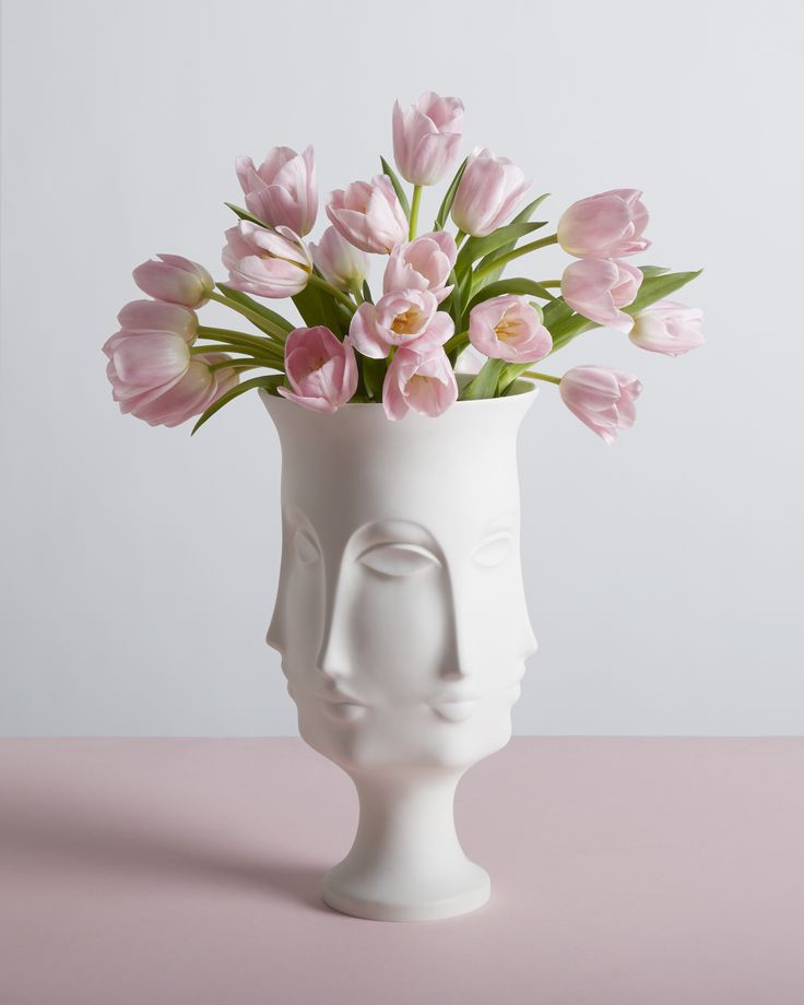 The Jonathan Adler Dora Maar Urn is a porcelain homage to the French photographer, poet, and painter best known for being a lover and muse of Pablo Picasso. This vase makes for a fabulous wedding gift as it is both bold and beautiful. Pictured with a bouquet of pink tulips.