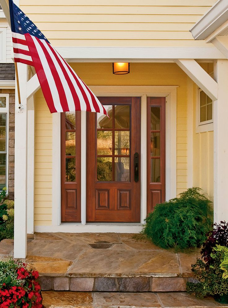 This premium fiberglass front door with 6 lite design and matching sidelights fill the this New England farmhouse style home with light and charm.