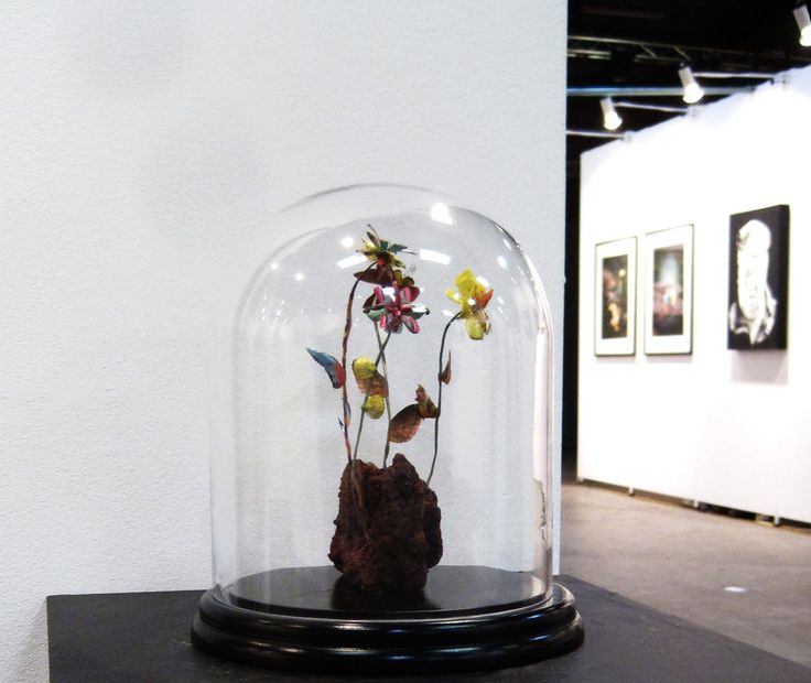 Erupting Flowers, DIA24 x H28 cm, in glassdome, 2016, Exhibition View - North Art Fair 2016 'Erupting Flowers' is the result of studies on Vestmannaeyjar, Iceland, more specifically Heimaey where I made geological research and tried to learn about, or rather imagined how plant life could have evolved after the violent eruptions from the 'Eldfell' volcano in 1973. The flowers in the work are cut and created entirely from illustrations of animals.  Iben Toft Nørgård
