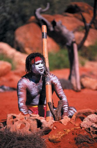 Australian Aboriginal with his wind instrument; a Didgeridoo. It is blown into making assorted drone sounds. Very essential in many Aboriginal ceremonies.