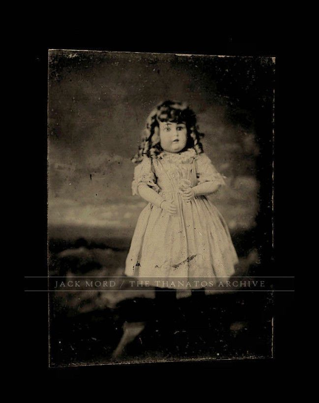 antique tintype photo of small doll standing on its own holding flower - CREEPY!
