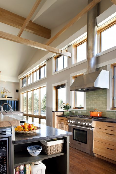 A house of modest size feels larger because of the tall cathedral ceiling that follows the roof slope. The kitchen in this new house has a custom wood trellis that anchors the space, brings...