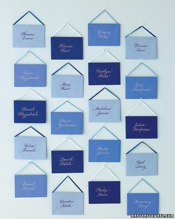 Envelopes in various hues hang from white ball pins with mixed and matched ribbon. Inside are cards with calligraphed table numbers. Staggering colors create a dynamic display.