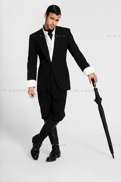 A Young Man In A Black Suit And Riding Boots Leaning On An