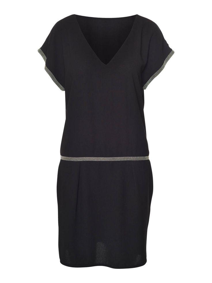 Zwarte jurk in crêpe met studs als afwerking aan mouwen en de taille. Steekzakjes aan de zijkant. Los bovenstukje, valt gedrapeerd. De pop draagt een S.  De jurk meet 89 cm vanaf de schouders tot aan de onderzijde.